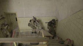 Operación parcial de los guerreros de la guerrilla en el ambiente urbano Soldados que entran en el edificio almacen de video