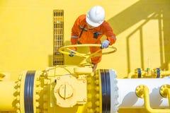 Operaciones costeras del petróleo y gas, válvula abierta del operador de la producción para permitir el gas que fluye a la línea  Fotos de archivo libres de regalías
