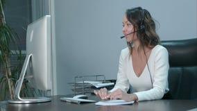 Operador asiático novo que fala com o cliente no centro de atendimento internacional vídeos de arquivo