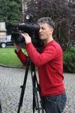 Operador da câmera que trabalha com uma câmara de televisão da transmissão do cinema Imagem de Stock Royalty Free