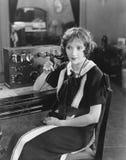Operador de centralita telefónica que se sienta en la centralita telefónica del teléfono y el hablar (todas las personas represen Foto de archivo
