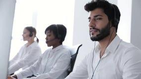Operador de centro de atención telefónica Hombre en el funcionamiento de las auriculares en el centro del contacto almacen de metraje de vídeo