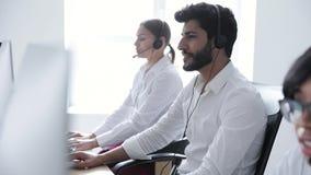 Operador de centro de atención telefónica Hombre en el funcionamiento de las auriculares en el centro del contacto almacen de video
