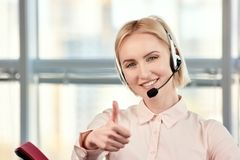 Operador de centro de atención telefónica maduro rubio de sexo femenino que muestra los pulgares para arriba Imagenes de archivo