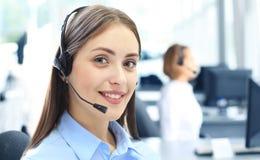 Operador de centro de atención telefónica de sexo femenino joven hermoso con las auriculares en oficina Imagen de archivo