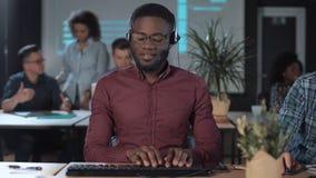 Operador de centro de atendimento alegre dos homens no trabalho video estoque