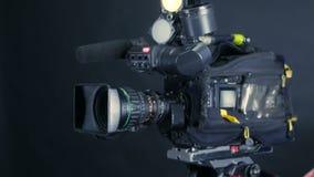Operador de la cámara que trabaja con una cámara de la difusión del cine en el estudio irreconocible de las noticias de la TV almacen de metraje de vídeo