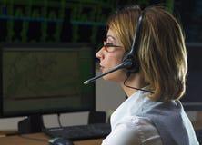 Operador de sexo femenino con el auricular en ce del control de distribución de poder Foto de archivo libre de regalías
