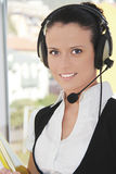 Operador de sexo femenino de la atención al cliente con el receptor de cabeza Fotos de archivo libres de regalías
