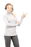Operador de sexo femenino del servicio de atención al cliente con los auriculares que señala con f Imagen de archivo