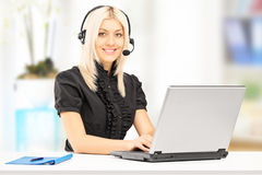 Operador de sexo femenino joven del servicio de atención al cliente que trabaja en el ordenador portátil Imagen de archivo libre de regalías