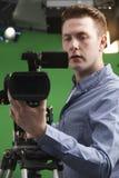 Operador de sexo masculino de la cámara en estudio de la televisión Imagen de archivo libre de regalías