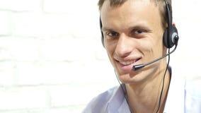 Operador de sexo masculino sonriente de la atención al cliente con las auriculares metrajes