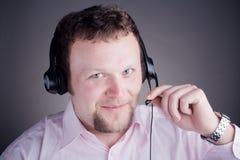 Operador de sexo masculino sonriente del servicio de atención al cliente en receptor de cabeza fotos de archivo