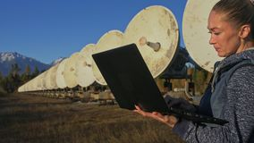 Operador del estudiante de mujer del instituto del equipo de comunicación terrestre solar de los monitores de la física en cuader almacen de metraje de vídeo