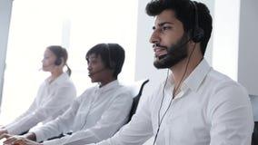 Operador do centro de chamadas Homem no funcionamento dos auriculares no centro do contato video estoque