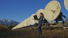 Operador do estudante de mulher do instituto do equipamento de comunicação terrestre solar dos monitores da física no caderno ori vídeos de arquivo