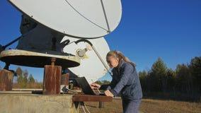 Operador do estudante de mulher do instituto do equipamento de comunicação terrestre solar dos monitores da física no caderno ori video estoque