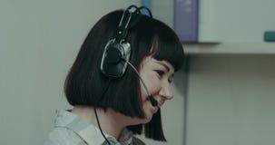 Operador fêmea consideravelmente novo que fala com o cliente no centro de atendimento usando os auriculares filme