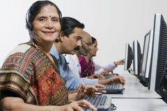 Operador fêmea do serviço ao cliente em Sari With Colleagues In Office fotografia de stock
