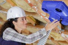 Operador fêmea que inspeciona as tubulações do condicionamento de ar foto de stock