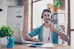 Operador joven sonriente del centro de atención telefónica que se sienta en la tabla y el s fotografía de archivo libre de regalías