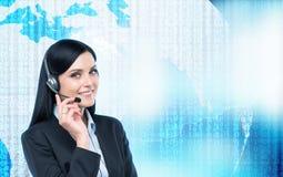 Operador moreno do apoio nos auriculares e no mundo digital com código binário no fundo Fotos de Stock