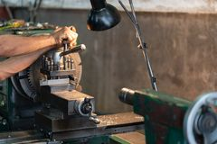 Operador profissional: equipe a máquina de moedura de funcionamento do torno - conceito metalúrgico da indústria Lath do controle foto de stock