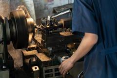 Operador profissional: equipe a máquina de moedura de funcionamento do torno - conceito metalúrgico da indústria Lath do controle fotografia de stock royalty free