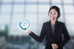 Operador sonriente feliz de la atención al cliente de las mujeres de Asia con las auriculares Imágenes de archivo libres de regalías