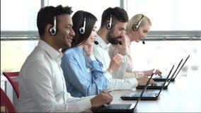 Operadores com os auriculares no escritório brilhante filme