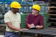 Operai che discutono con una lavagna per appunti in impianto di produzione delle bevande Immagine Stock Libera da Diritti