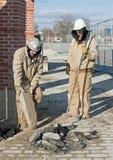 Operai che rimuovono pavimentazione Fotografie Stock