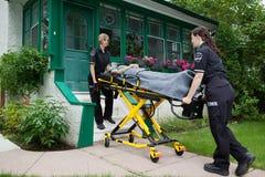 Operai dell'ambulanza con la donna maggiore Fotografie Stock