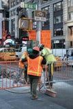 Operai veduti rimuovere le vecchie lastre per pavimentazione in New York, U.S.A. fotografia stock