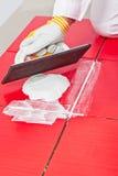 Operaio che applica le mattonelle del trowel del briciolo della malta liquida Immagini Stock Libere da Diritti