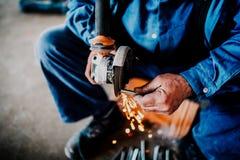 operaio che lavora e che taglia ferro d'acciaio con la smerigliatrice di angolo fotografia stock