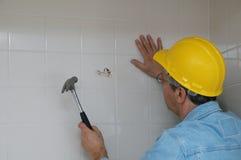Operaio che rompe in su una parete della stanza da bagno Immagini Stock