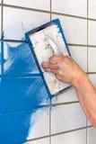 Operaio che si applica malta liquida blu alle mattonelle bianche Fotografie Stock Libere da Diritti
