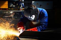 Operaio con la molatura dei guanti e della mascherina protettiva Fotografia Stock