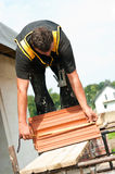 Operaio con le mattonelle di tetto Fotografia Stock