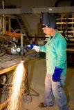 Operaio del metallo che per mezzo del bruciatore della pista fotografia stock