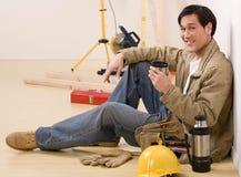 Operaio di costruzione che cattura un intervallo per il caffè Fotografia Stock