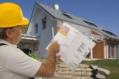 Operaio di costruzione con il programma di un architetto Immagine Stock