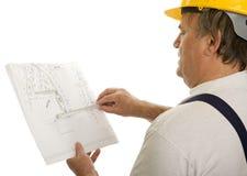 Operaio di costruzione con il programma di un architetto Immagini Stock
