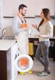 Operaio e cliente vicino alla lavatrice Immagine Stock