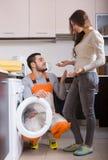 Operaio e cliente vicino alla lavatrice Fotografia Stock