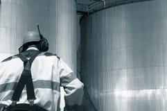 Operaio e serbatoi di combustibile dell'olio Immagini Stock