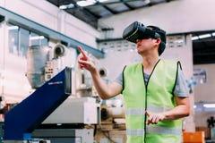 Operaio industriale che indossa gli occhiali di protezione di VR che toccano in mondo di realtà virtuale dentro la fabbrica immagini stock libere da diritti