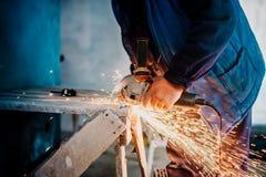 Operaio metallurgico che usando piccola smerigliatrice elettrica e tagliando metallo immagini stock